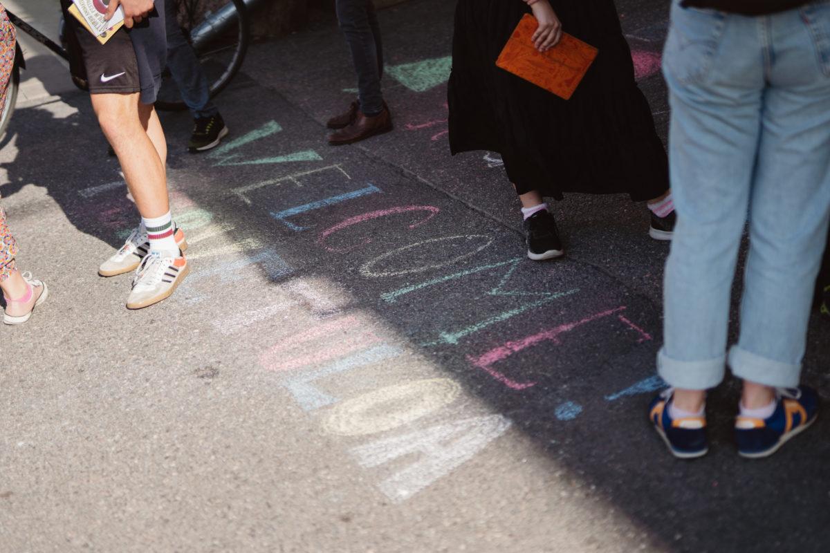 """Kuvassa jalkakäytävälle on kirjoitettu värikkäin kirjaimin """"WELCOME! TERVETULOA"""". Tekstin ympärillä näkyy ihmisten jalkoja sandaaleissa ja kesäkengissä."""
