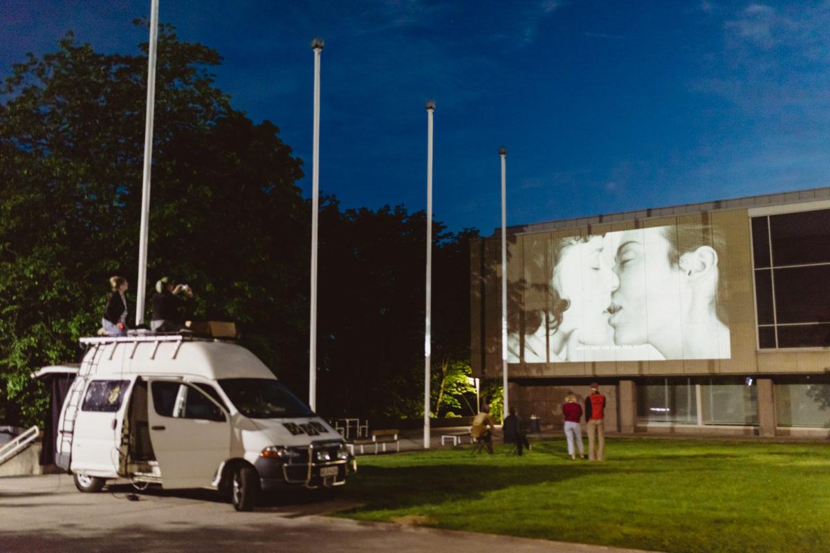 Kuvassa näkyy yliopiston seinään heijastettu video, jossa kaksi ihmistä suutelee. Ihmisiä katsoo videota nurmialueella seinän edessä sekä kauemmaksi parkeeratun pakettiauton katolla istuen.
