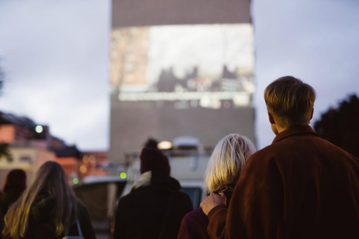 Ihmiset katsovat elokuvaa, joka on heijastettu rakennuksen seinään.