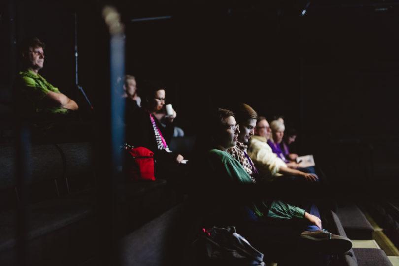 Noin kymmenen katsojaa katsovat eteenpäin teatterin penkeillä. Sali on pimeä, mutta katsojien kasvoille heijastuu valoa valkokankaalta.