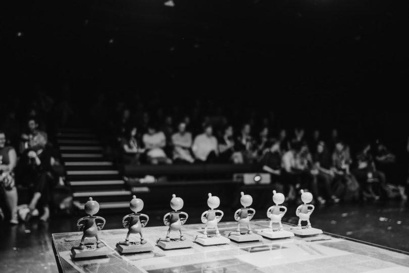 Kuvassa rivi palkintoja valaistulla pöydällä. Taka-alalla näkyy katsomo, jossa ihmisiä.